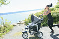 A Young mother jogging with a baby buggy Royalty Free Stock Photo