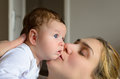 Young mother kissing her adorable baby boy in a room Royalty Free Stock Photos