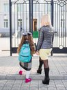 Mother brought her daughter to school, view from behind, Concept family