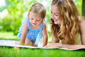 Young mother with little daughter reading book in park Royalty Free Stock Photo