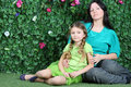 Young mother and little daughter sit on grass in garden next to verdant fence Stock Photo
