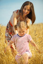 Young mother with little daughter at wheat field Royalty Free Stock Photo