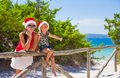 Young mother and little girl in red christmas hat santa at tropical beach Stock Photo