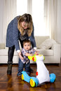 Young mother and little one year old son walking with baby walker taking his first brave steps Royalty Free Stock Photo