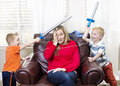 Young mother overwhelmed by her kids with home life as two little boys have a sword fight around Stock Image