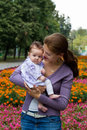 Young mother playing with her adorable baby in a park Royalty Free Stock Photography