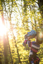 Young mother playing in woodland with her baby holding the infant aloft as the warm bright glow of the sun back lights them Royalty Free Stock Images