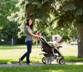 Young mother pushing stroller in park full length portrait of the Stock Image