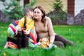 Young mother sitting with daughter on a lawn Stock Photo