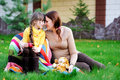 Young mother sitting with daughter on a lawn Royalty Free Stock Photography
