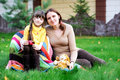 Young mother sitting with daughter on a lawn Stock Photography