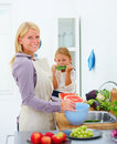 Young mother smiling and her daughter eating Stock Images