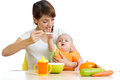 Young mother spoon feeding her baby girl Stock Image