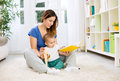 Young mother telling a story to her baby and giving banana for s Royalty Free Stock Photo