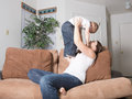 Young mother and toddler son at home playtime her in living room engaging in interactive horseplay she is lifting her high in the Stock Photo