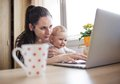 Young mother working from home in office with computer and her daugher Stock Images