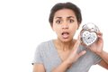 Young mulatto girl posing with alarm clock oh my god portrait of youthful pleasant holding near her face on white isolated Royalty Free Stock Photography