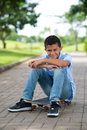 Young mulatto guy vertical portrait of sitting on the skateboard in the park Royalty Free Stock Images