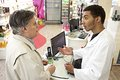 Young mulatto male pharmacist speaking with a customer at at pharmacy Royalty Free Stock Photography