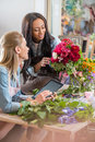 Young multiethnic florists working with digital tablet and flowers in flower shop Royalty Free Stock Photo