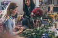 Young multiethnic florists working with flowers and digital tablet in flower shop Royalty Free Stock Photo