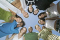 Young multiethnic friends forming a circle low angle group portrait of in against the sky Stock Photography