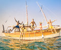 Young multiracial friends jumping from wooden sailboat Royalty Free Stock Photo