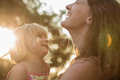 Young mum holding his blonde daughter girl on his arms and laughing or smiling. Warm sunset light. Family summer travel Royalty Free Stock Photo