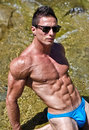 Young muscle man outdoors in water showing muscular abs pecs and arms wearing sunglasses Stock Images