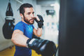 Young muscular kickboxing fighter practicing kicks with punching bag.Kick boxer boxing as exercise for the fight.Boxer Royalty Free Stock Photo