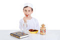 Young muslim boy eating dates for brakfast in ramadan sitting on a table with water quran and lantern Royalty Free Stock Photo