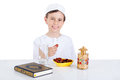 Young muslim boy holding dates ready for brakfast in ramadan sitting on a table with water quran and lantern Royalty Free Stock Images