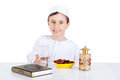 Young muslim boy ready for brakfast in ramadan sitting on a table with water dates quran and lantern Royalty Free Stock Image