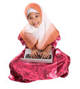 Young muslim girl sitting with laptop iv asian on a floor over white background Royalty Free Stock Photo