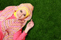 Young muslim girl wearing hijab lying on grass with copy space portrait of Royalty Free Stock Photography