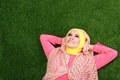 Young muslim girl wearing hijab lying on grass and looking up portrait of Royalty Free Stock Photography