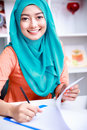 Young muslim woman smiling while writing on a paper Royalty Free Stock Photo