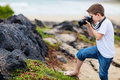 Young nature photographer little boy photographing marine iguanas on volcanic rocks Royalty Free Stock Photography