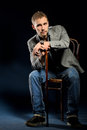 Young negligent man with cane sitting on chair portrait of dark studio background Stock Photography