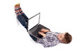Young nerd boy lying on floor using a laptop with empty white sc Royalty Free Stock Photo