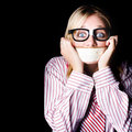 Young nerdy woman wearing eyeglasses fearful with tape across her mouth Royalty Free Stock Photo