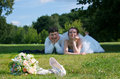 Young newlywed couple liying on a green grass Stock Photos