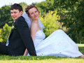 Young newlywed couple sitting on a green grass Stock Photos
