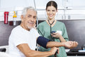 Young nurse checking blood pressure of senior patient smiling male in rehab center Stock Photos