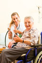 Young nurse and female senior in nursing home the blood pressure is going to be measured Royalty Free Stock Photos