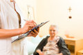 Young nurse and female senior in nursing home measurements are taken or administrative duties taken care of Stock Photos
