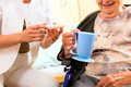 Young nurse and female senior in nursing home the old lady sitting a wheel chair Royalty Free Stock Images