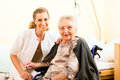 Young nurse and female senior in nursing home the old lady sitting a wheel chair Royalty Free Stock Photos