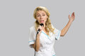 Young nurse gesticulating holding microphone. Royalty Free Stock Photo