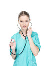 Young nurse using stethoscope and looking at camera Royalty Free Stock Photo